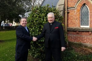 Photo of Shane Foster and Father Hugh Bowron shaking hands.